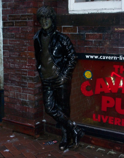 A rather poor statue of John Lennon outside The Cavern Pub. Also, each brick in the wall has the name of a band that has performed at The Cavern Club, Liverpool (2006)
