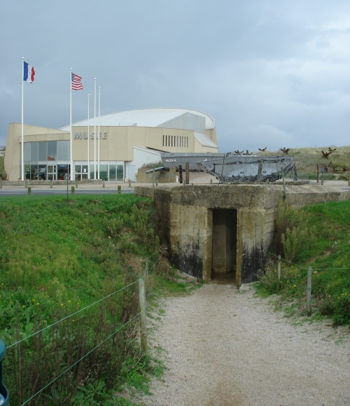 An authentic bunker at Utah beach. An impressive D-Day museum in the background, France (2006)